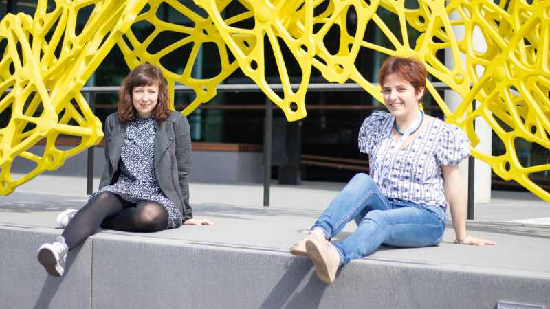 Two PhD students sitting on a concrete block in front of a yellow metal sculpture